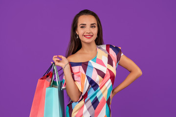 Beautiful young woman with colorful shopping bags on the wonderful purple background