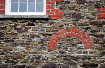 Brickwork arch and window surround or mullion, in red brick, in an old stone built wall