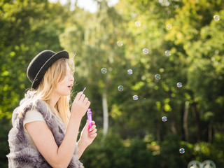 Joyful teen woman blowing bubbles