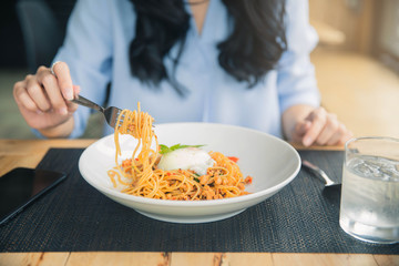 Spaghetti on a fork. Girl keeping fork with spaghetti.  Young woman eating Italian pasta.