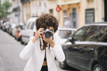 Afro-haired latin girl taking pictures with classic camera.