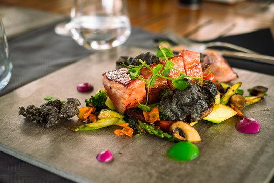 Mini tuna steaks with salad potato side dish and vegetables on ceramic plate