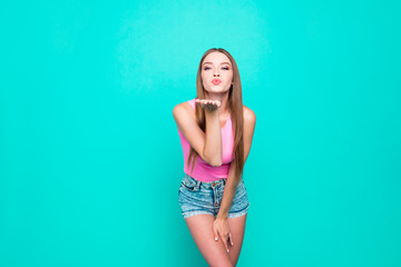 Portrait of girl in jeans shorts sending an air kiss from an ope