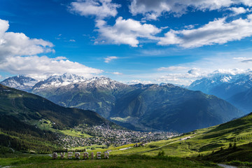 Scenery view of Verbier village surrounded with beautiful Swiss Alps mountains in sunny summer day with green meadows, forests, blue sky.