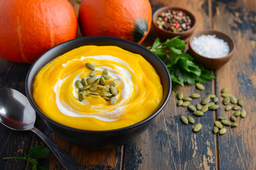 Pumpkin cream soup with cream and pumpkin seeds on rustic wooden table.