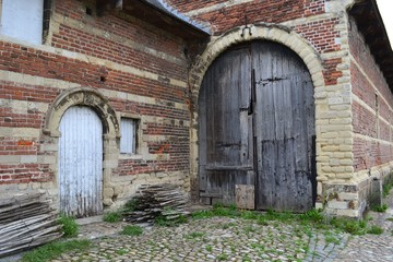 Photograph of a gate of old brick-and-limestone stables. Taken at Park Abbey, Leuven, Belgium.