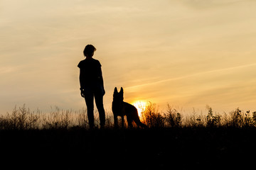 Girl and dog at sunset .
