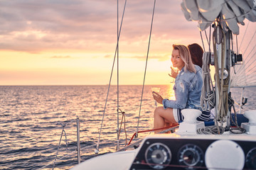 Female friends relaxing on the yacht with glasses of wine in the hands, during sunset on the high seas.