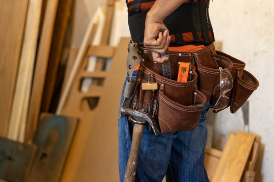 Man with tool belt in a workshop