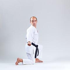 Athlete in white karategi trains formal karate exercises on a gray background