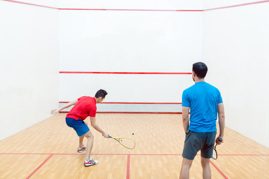 Rear view of two competitive young men with a modern lifestyle playing doubles squash game on a professional court