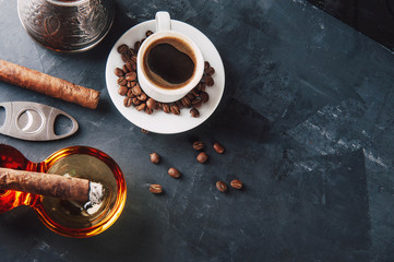 Cup of coffee, coffee beans, ashtray with cigar on dark background