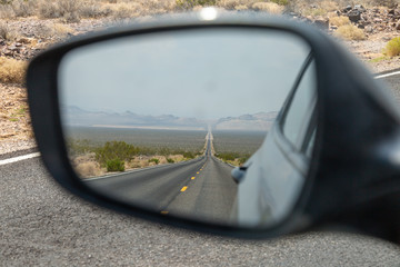 Looking into the rear view mirror of a car, at a long, straight road in Death Valley, California