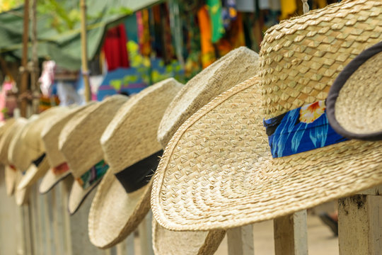 Summer beach hats on display at craft market for sale, decorated with caribbean and tropical colors