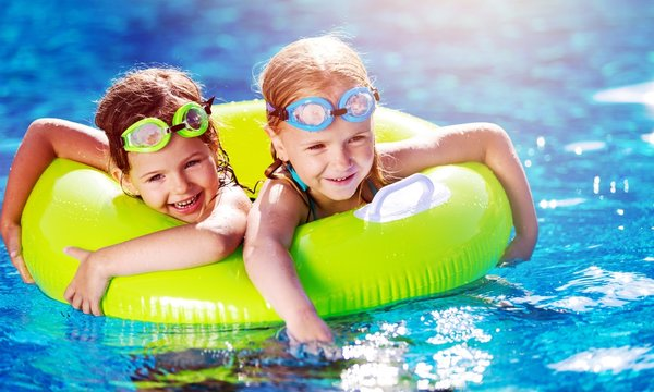 Children playing in pool. Two little girls having fun in the
