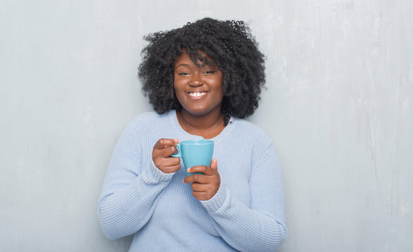 Young african american woman over grey grunge wall drinking a cup of coffee with a happy face standing and smiling with a confident smile showing teeth