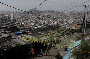 Residents walk at the Chatuba slum in Rio de Janeiro