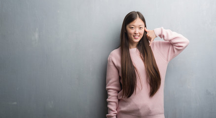 Young Chinese woman over grey wall smiling doing phone gesture with hand and fingers like talking on the telephone. Communicating concepts.