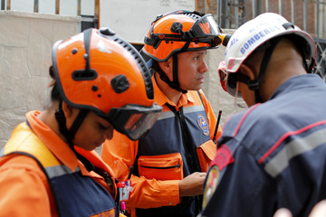 """Venezuelan Civil Protection members and firefighters stand at an entrance of the skyscraper known as the """"Tower of David"""" during an inspection after an earthquake in Caracas"""