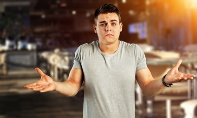Portrait young man shrugging shoulders