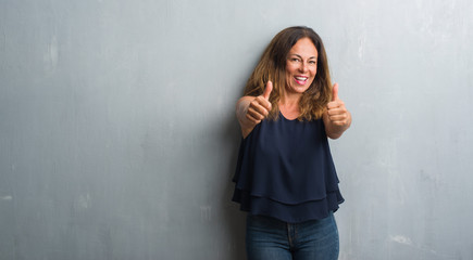Middle age hispanic woman standing over grey grunge wall approving doing positive gesture with hand, thumbs up smiling and happy for success. Looking at the camera, winner gesture.