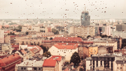 Raindrops on the dirty glass, behind the glass blurred panorama of the old bright colored city, abstract cozy retro nostalgically background