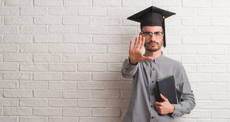 Young adult man over brick wall wearing graduation cap with open hand doing stop sign with serious and confident expression, defense gesture