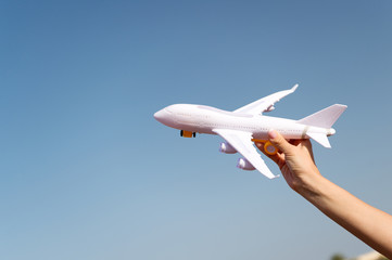 Plane in female hand clear blue sky background copy space. Travel and vacation. Book tickets now. Toy white plane fly vacation destinations. Travel comfortable premium class airlines. Discover world
