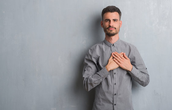 Young adult man standing over grey grunge wall smiling with hands on chest with closed eyes and grateful gesture on face. Health concept.