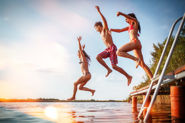 Group of friends jumping into the lake from wooden pier.Having fun on summer day. Fotomurales