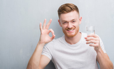 Young redhead man over grey grunge wall drinking water doing ok sign with fingers, excellent symbol