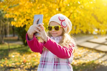 Pretty girl of 7 years doing selfie using a smartphone.