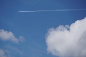 Flugzeug mit Kondensstreifen im Himmel vor Wolken