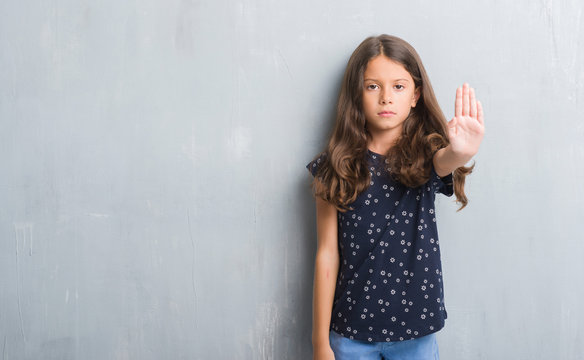 Young hispanic kid over grunge grey wall doing stop sing with palm of the hand. Warning expression with negative and serious gesture on the face.