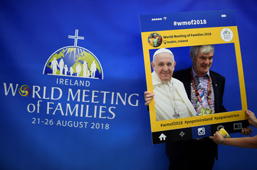 A woman holds a frame of Pope Francis in front of a man for his friend to take a picture at the Pastoral Congress at the World Meeting of Families in Dublin