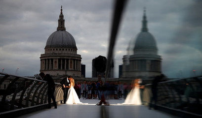 A bride and groom pose for photographs on the Millennium Bridge with St Paul's Cathedral as a backdrop in London.