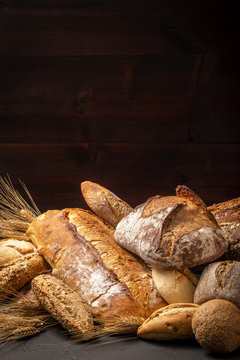 Composition of abundance of freshly baked loaves of bread and buns with ears of wheat