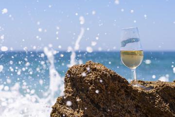 Copa de vino en la playa con olas salpicando
