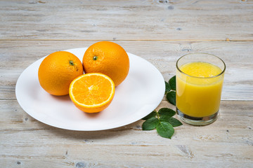 Fresh oranges on a white plate on a rustic wooden table and glass of juice close-up.