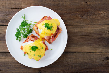 Eggs benedict with bacon on wooden background . Top view