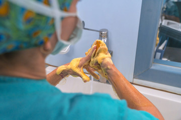 Surgeon washing her hands before surgery