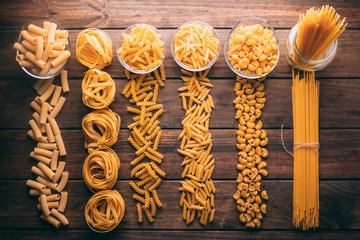 Top view of a rustic wooden table full of different types of pasta, Carbohydrates