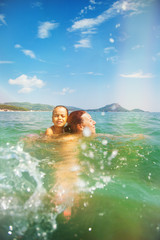 Mother and daughter swim in the beautiful sea, enjoy and have fun on vacation