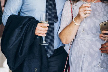 hands of stylish people cheering with glasses of champagne, luxury wedding reception, rich celebration.  guests toasting at christmas luxury celebration feast