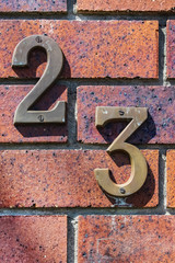 Close-up of grungy number 23 screwed onto distressed brick