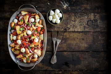Prepared healthy salad with vegetables,baked bread and mozzarella served on the wooden background with blank space,selective focus