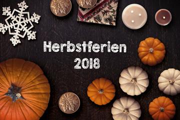 """Holzuntergrund mit Aufschrift """"Herbstferien 2018"""" und herbstlicher Dekoration"""