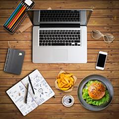 Businessplan in Notizbuch und Arbeitsplatz mit Computer, Burger und Smartphone