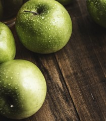 Set of green apples on a wooden table