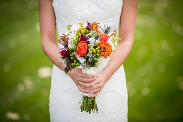 Wedding flowers, bride, bouquet, white dress, holding a bouquet of flowers, grass background, bridesmaid
